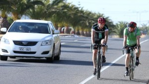 two cyclists on a road and a white car driving
